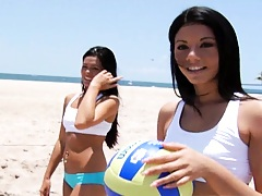 Sexy chicks in tight shorts playing volleyball on beach