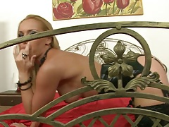 Posing blonde Cathy Campbell solo on the bed with finger in pussy hole