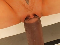 Close up of a fat dildo going inside this poor girl